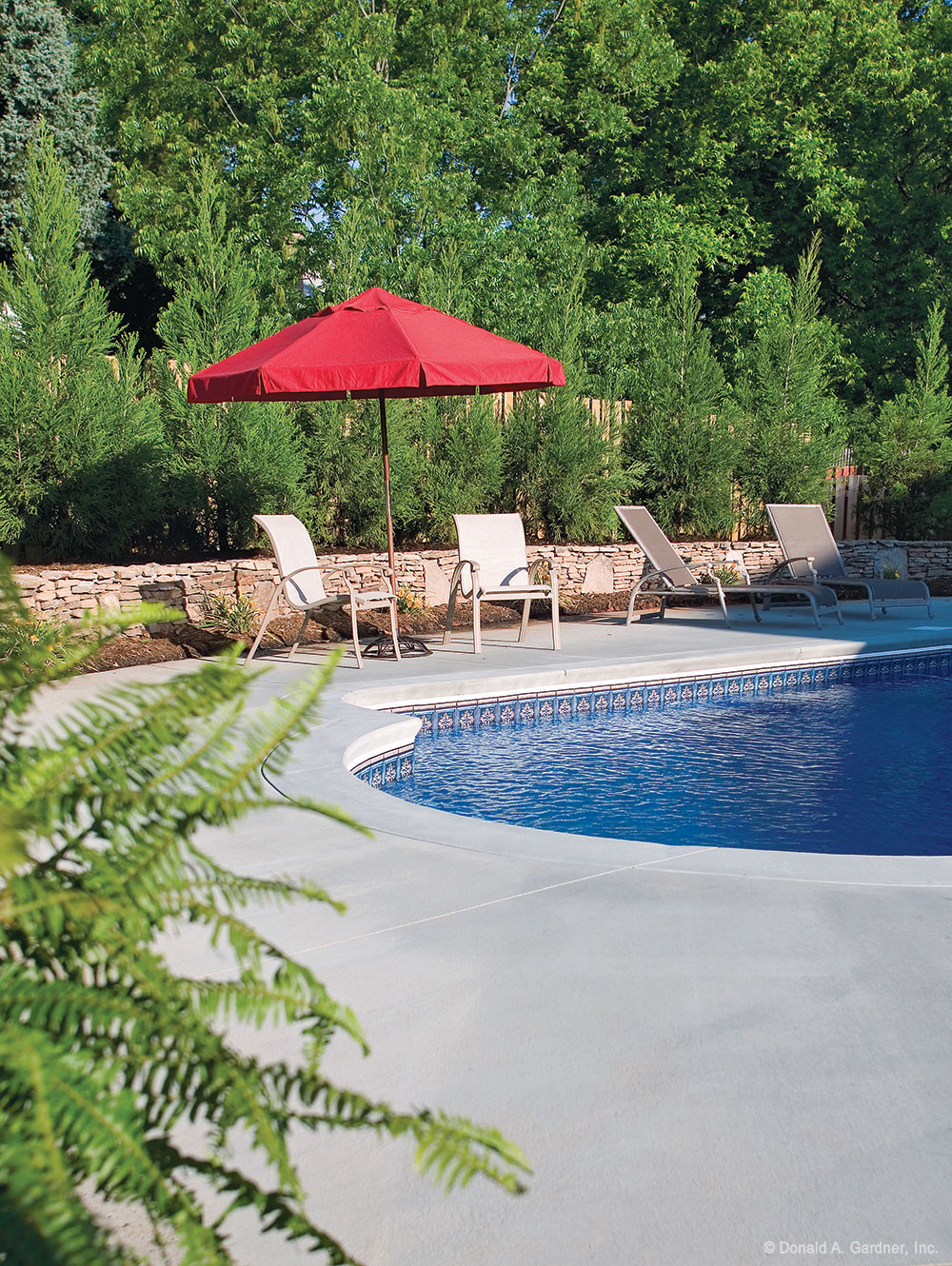 Privacy Features: Backyard pool of the Churchdown Plan #867, surrounded by a stone wall, privacy fence, and tall plans to provide privacy.